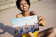 Happy woman showing postcard of New York City - GIOF001429