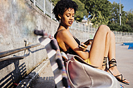 Young woman sitting on bench looking at cell phone - GIOF001432