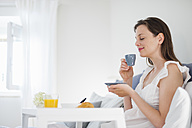 Woman sitting in bed with breakfast tray - DIGF000949