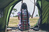 Back view of young woman sitting in a tent looking at distance - DAPF000258
