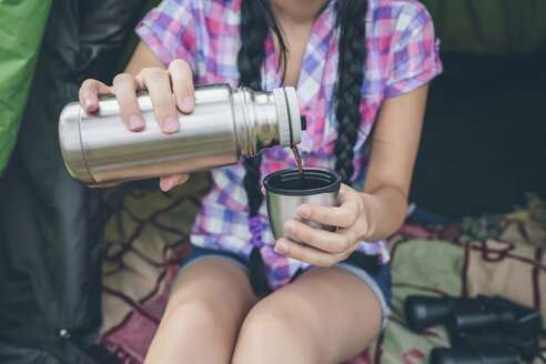 Young woman sitting in a tent pouring coffee from thermos flask into cup, partial view - DAPF000261