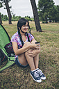 Young woman sitting in front of a tent with cup of coffee - DAPF000264