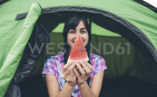 Young woman in front of a tent holding piece of watermelon - DAPF000267