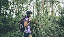 Smiling young woman with backpack  walking in the forest - DAPF000270
