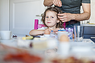 Father doing daughter's hair at breakfast table - DIGF000955