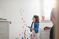 Girl looking at decorated wall in children's room - DIGF000970