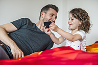Father and daughter with cell phone on bed - DIGF000988