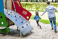 Father running with daughter on playground - DIGF001006