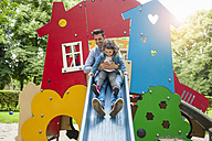 Father with daughter on playground slide - DIGF001024