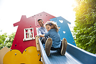 Father with daughter on playground slide - DIGF001027