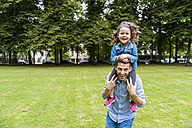 Father carrying daughter on shoulders in park - DIGF001033