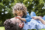 Father cuddling with daughter on meadow in park - DIGF001039