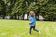 Happy girl running on meadow in park - DIGF001045