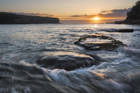 Australia, New South Wales, seascape with rushing water and rising sun and backlit, waves - GOAF000011