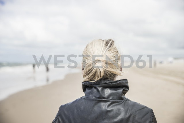 Back view of woman wearing leather jacket on the beach - CHPF000285