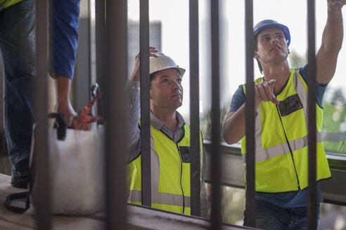 Men with reflective vests talking on construction site - ZEF009430