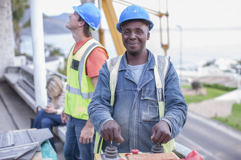 Smiling construction worker operating machine - ZEF009460
