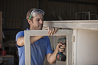 Carpenter using a cordless drill at a cabinet - ZEF009526