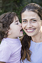 Portrait of happy mother with little daughter kissing her - ABZF000987