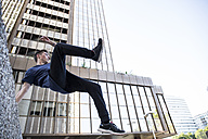Spain, Madrid, man jumping over a wall in the city during a parkour session - ABZF000996