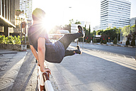 Spain, Madrid, man jumping over a fence in the city during a parkour session - ABZF001002