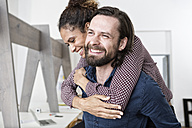 Man carrying happy woman piggyback in office - RBF004911