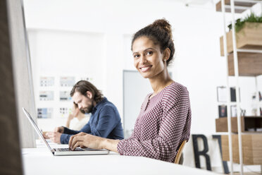 Smiling woman in office working on laptop - RBF004914