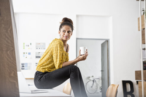 Smiling woman sitting on office desk holding cup - RBF004938