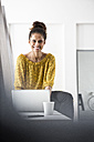 Smiling woman sitting on office desk using laptop - RBF004941
