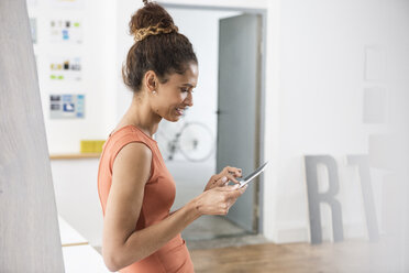 Smiling woman using digital tablet in office - RBF004956