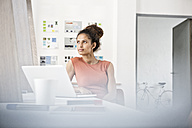 Woman sitting at office desk thinking - RBF004959