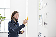 Man in office writing on adhesive notes on wall - RBF004968