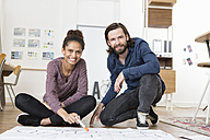 Portrait of two smiling colleagues on office floor with construction plan - RBF004974