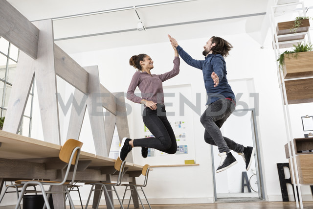 Two happy colleagues in office jumping and high fiving - RBF004977 - Rainer Berg/Westend61