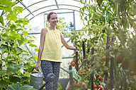 Woman with watering can in a greenhouse - KNTF000441