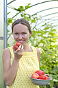 Portrait of happy woman with bowl of harvested tomatoes in front of greenhouse - KNTF000444
