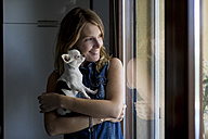 Smiling woman with dog on her arms looking through window - MAUF000810