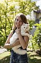 Happy woman with cat on her arms in the garden - MAUF000816