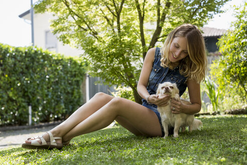 Happy woman sitting on meadow in the garden with her Chihuahua - MAUF000825
