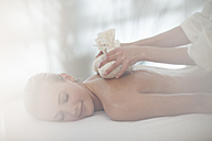 Masseuse placing aromatherapy sachets on woman's back - ZEF009568