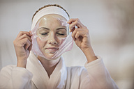 Young woman at spa removing facial mask - ZEF009589