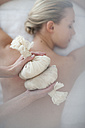 Masseuse holding aromatherapy sachets over woman's back - ZEF009595