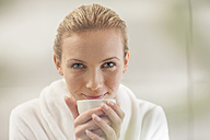 Portrait of smiling young woman in bathrobe drinking tea - ZEF009604