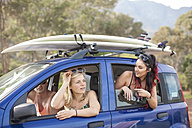 Friends omn a trip in car with surfboards on roof - ZEF009619