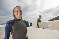 Smiling young woman with surfboard on the beach - ZEF009631