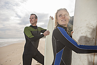Couple with surfboards on the beach looking around - ZEF009634
