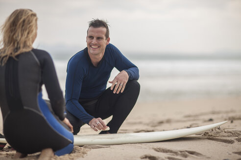 Couple with surfboard on the beach - ZEF009637