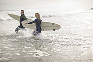 Couple with surfboards running together through the waves - ZEF009640