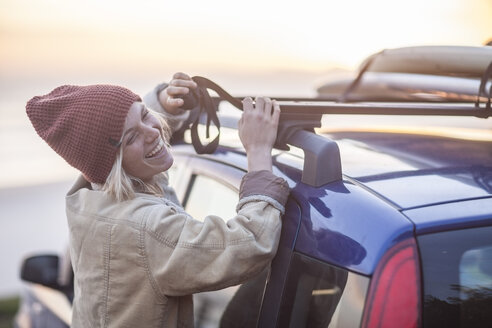 Happy young woman wearing warm clothes fastening surfboard on car roof - ZEF009649