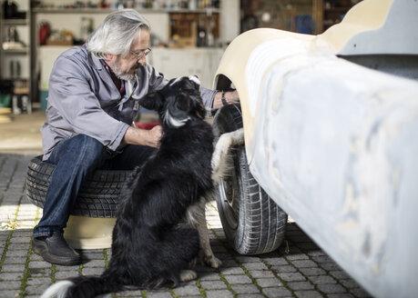 Senior man with dog examining car tyre - ZEF009655